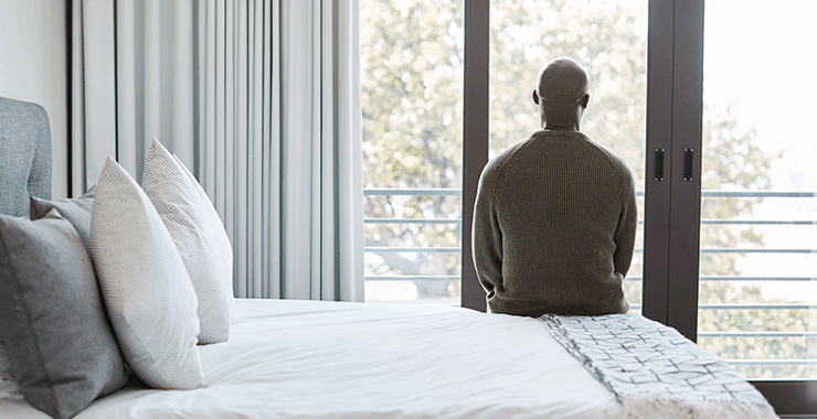 man sitting alone on a bed