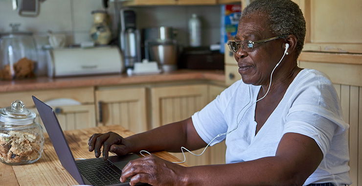 Elderly woman with headphones looks her computer