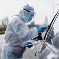 Medical personnel in full PPE equipment checking a drivers temperature
