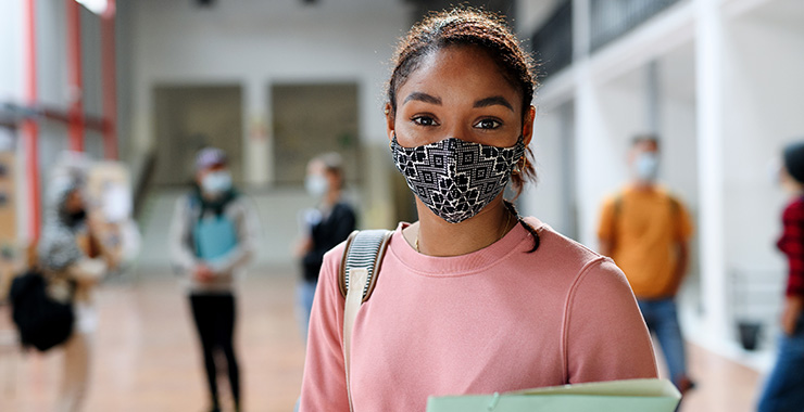 Female student wearing a face mask and holding a binder
